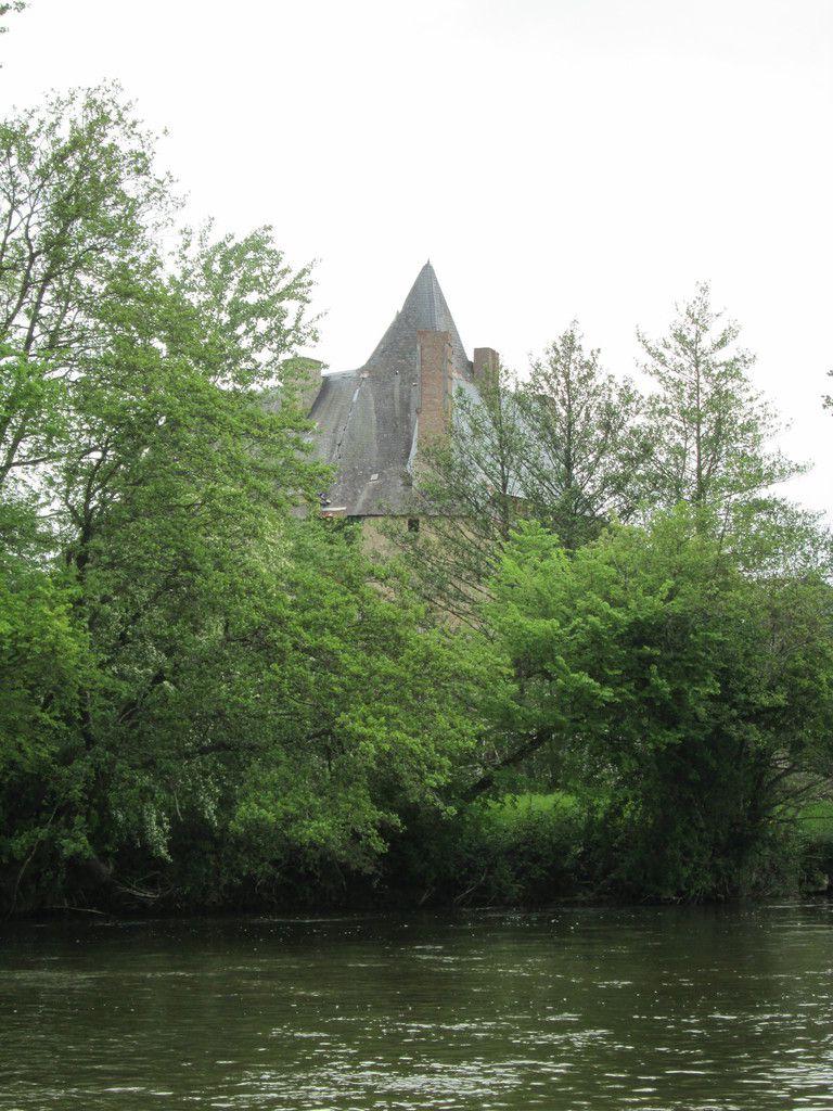 Côté rivière, derrière de grands arbres, le château se devine et semble en embuscade
