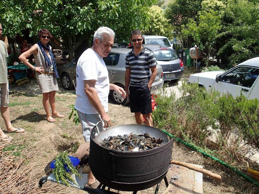 Préparation des moules au râteau, on remarquera le balai de romarin qui imprègnera les moules de sauce.