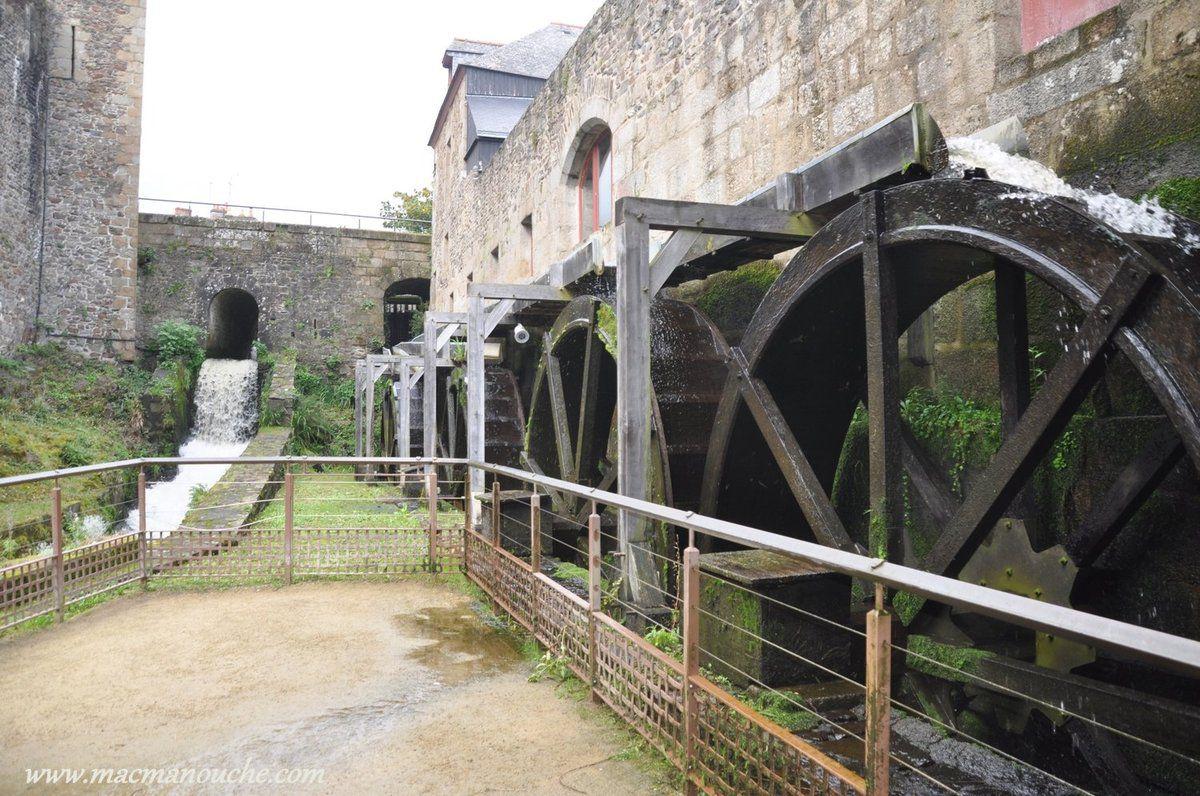 La rivière '' Le Nançon'' emplit les douves du château et entraîne un quadruple moulin à eau.