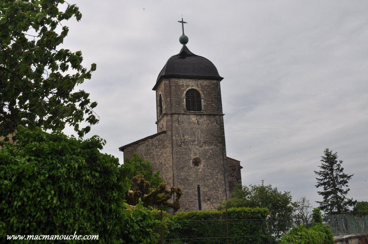 On approche de la cité médiévale dont on aperçoit le clocher.