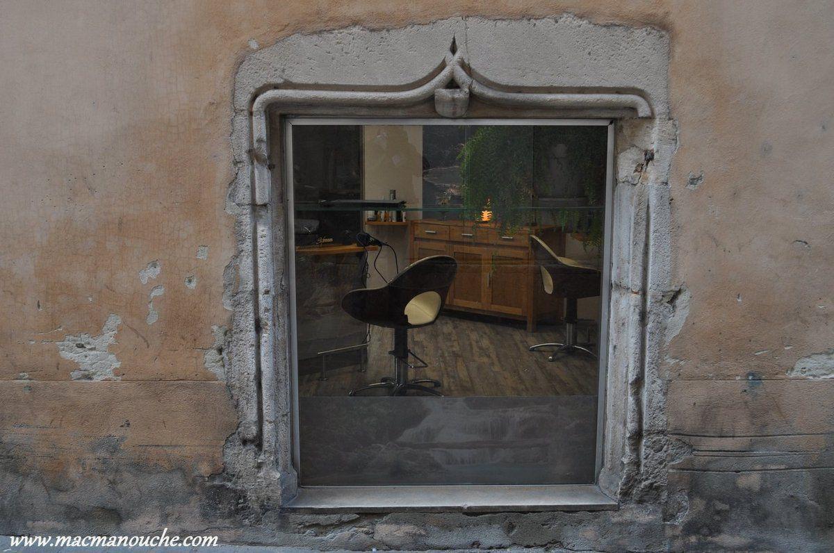 Fenêtre d'un salon de coiffure dans la rue du bac.