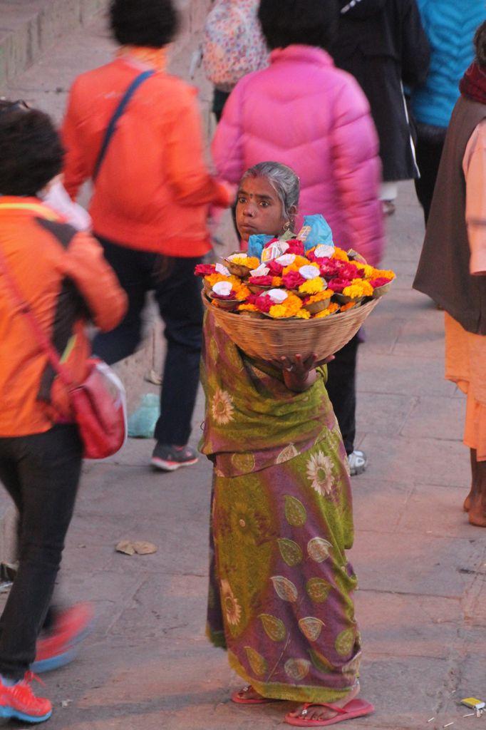 Une vendeuse d'offrandes à déposer au fil de l'eau