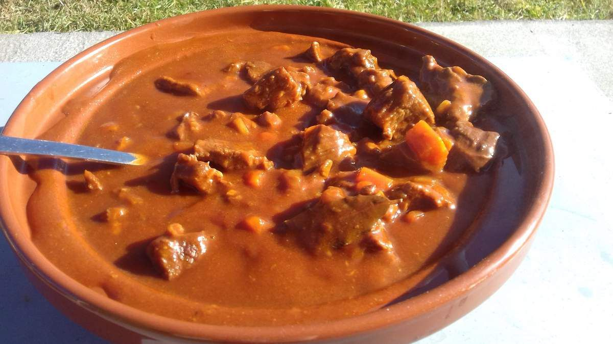 Le goulasch ou goulache ou encore soupe de goulasch est une spécialité d'Europe centrale que l'on retrouve dans plusieurs pays: la Hongrie, la Tchéquie, l'Autriche, l'Allemagne.  C'est un ragoût de viande, souvent du bœuf mais il existe aussi des recettes de goulasch à base de porc ou de veau. Les épices sont à l'honneur dans le goulasch: le paprika doux et fort, le cumin ainsi que la marjolaine parfument ce ragoût-soupe de viande.  Au niveau des légumes, les oignons, l'ail,  les poivrons, parfois les pommes de terre ou les carottes et la sauce tomate sont des ingrédients de base dans la préparation du goulache.  Pour réussir un bon goulasch, il faudra veiller à bien doser vos épices, paprika doux et fort, cumin et marjolaine. Mais aussi, il faudra bien faire mijoter le goulasch, 3 heures au moins, afin que la viande soit bien tendre et la sauce onctueuse ainsi que bien liée. (càd qu'elle épaississe).  Souvent servi avec des pommes de terre vapeur, de la purée ou encore des knedliky (grosses boulettes bouillies de pain)  Cet été, nous sommes partis en Tchéquie et en Autriche. Nous avons ainsi découvert le goulasch (et de multiples autres spécialités culinaires). j'avais donc envie de vous faire partager cette recette simple à réaliser.