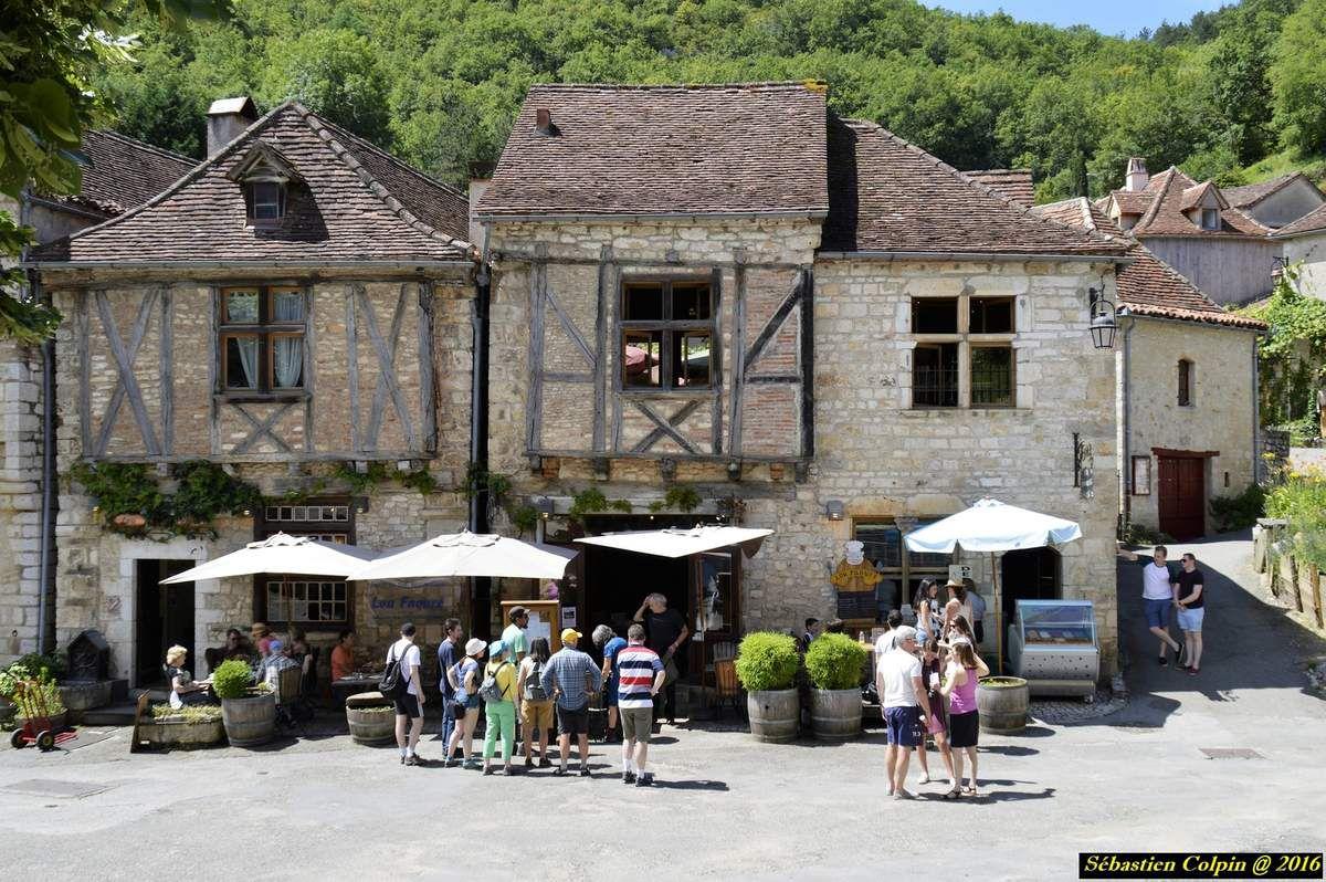 """Le bourg médiéval de Saint-Cirq Lapopie, qui compte 13 monuments historiques est l'un des plus beaux villages de France. Accroché sur une falaise à 100 mètres au-dessus du Lot, Saint-Cirq Lapopie constitue l'un des sites majeurs de la vallée du Lot.   Chef-lieu de l'une des trois vicomtés du Quercy, Saint-Cirq Lapopie fut partagé au Moyen Âge entre plusieurs dynasties féodales dont les familles dominantes de Lapopie, de Gourdon et de Cardaillac. De ce fait, plusieurs châteaux et maisons fortes constituaient le fort seigneurial et dominaient le village. En contrebas du fort, les rues du village, fermées par des portes fortifiées, ont conservé de nombreuses maisons anciennes dont les façades en pierre ou à pans de bois ont été construites entre le XIIIe et XVIe siècles. Étroites, elles sont caractérisées par leurs toits de tuiles plates, à fortes pentes. Les rues, où s'ouvrent des arcades d'échoppes, conservent le souvenir des activités artisanales qui firent la richesse de Saint-Cirq. Peaussiers de la rue de la Pélissaria, chaudronniers de la rue de la Peyrolerie et surtout tourneurs sur bois ou roubinetaïres, dont les ateliers produisaient les moules à boutons, écuelles, gobelets et robinets de tonnellerie.   L'Eglise de Saint-Cirq Lapopie dédiée à Saint Cyr (origine du """"Cirq"""" de Saint-Cirq Lapopie) et Sainte Julitte, sa mère. Il fut le martyr le plus jeune de la chrétienté ( 3 ans environ). C'est Saint Amadour qui en ramènera les reliques en France. L'église gothique qui fut édifiée à partir de 1522 a englobé l'ancienne église paroissiale romane. Celle-ci conserve les vestiges de son décor sculpté à feuille d'acanthe du XIIème siècle, ainsi que des fragments de peinture murales du XIIIème. Une des chapelles latérales de l'église est consacrée à Sainte Catherine, patronne des tourneurs sur bois. Près du portail, au pied du clocher fortifié, est conservée l'une des mesures de pierre qui règlementait la vente des grains sur le marché. Au revers de l'église, terrasses """