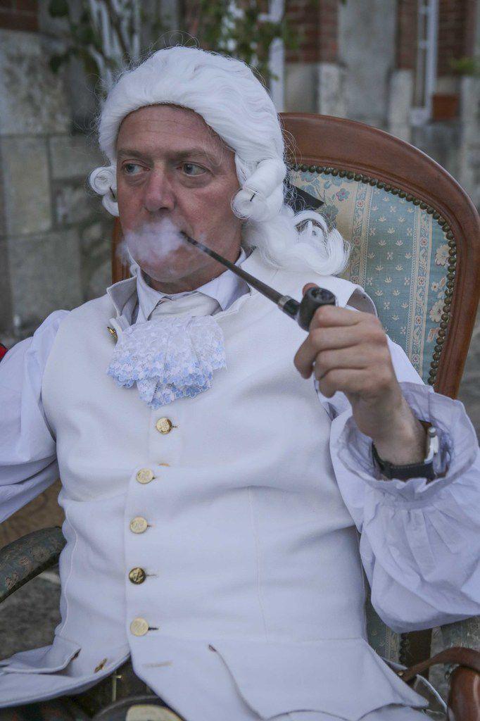 Enoch fume la pipe et arbore une perruque entre deux démonstrations de tir au pistol