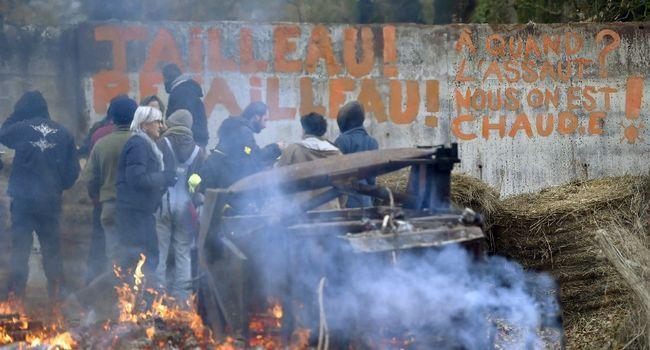 Des militants hostiles au projet d'aéroport nantais devant un slogan ciblant Bruno Retailleau, le président de la région Pays de la Loire, sur une barricade dans le territoire qu'ils occupent à Notre-Dame des Landes LOIC VENANCE  /  AFP/Archives