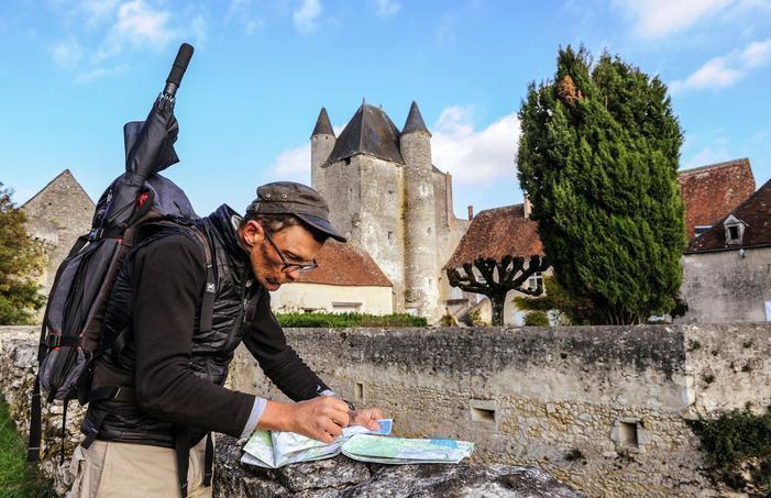 Dans un village au sud de Chateauroux, devant le parapet d'une douve qui sert de support pour déployer une carte. Crédits photo : Thomas Goisque pour le Figaro Magazine