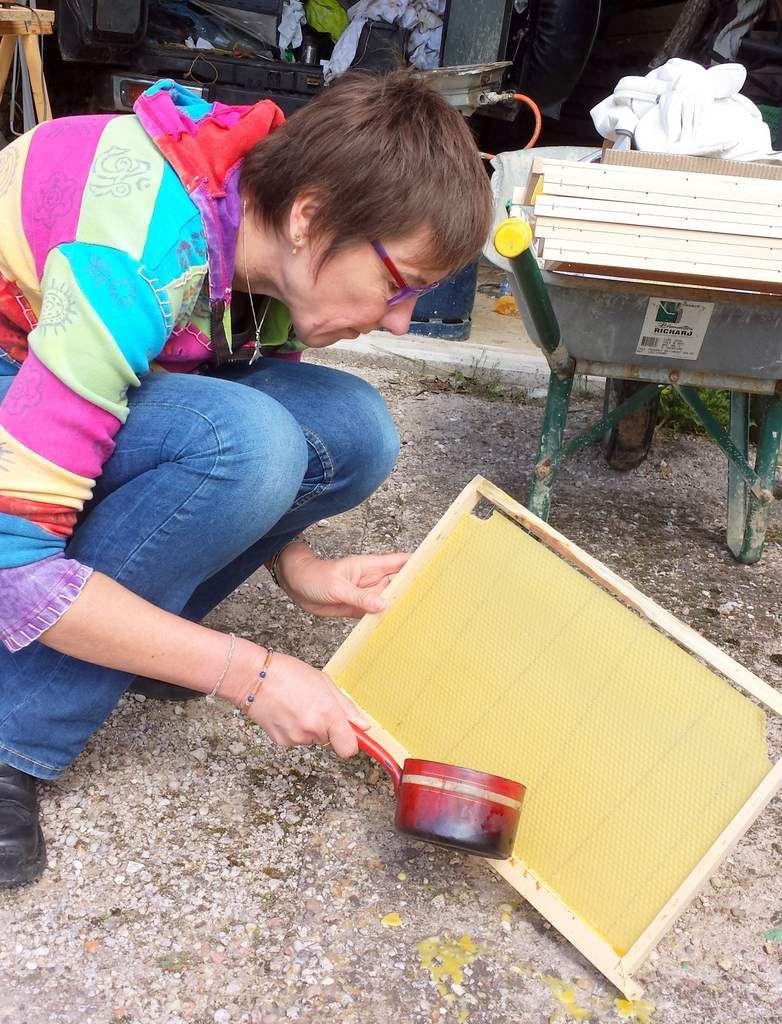 cire fondue délicatement coulée pour solidifier la feuille de cire sur le cadre
