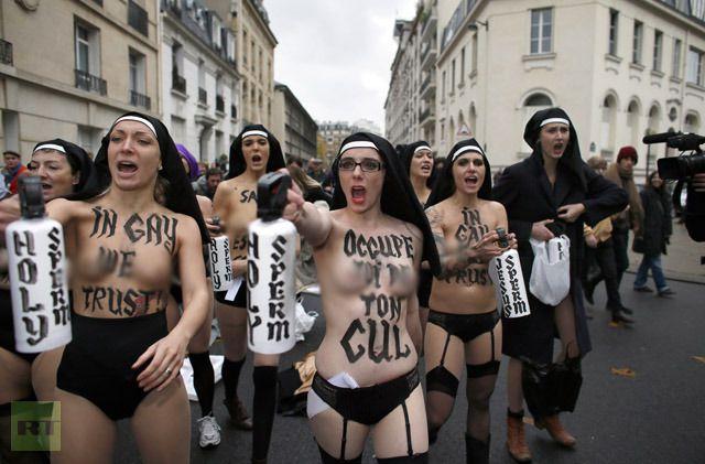 """Action dans la rue où peut encore lire sur leurs corps """"In gay we trust"""", alors qu'elles tiennent des gazeuses lacrymogènes sur lesquelles ont peut """"Holy sperm"""" (saint sperme)"""