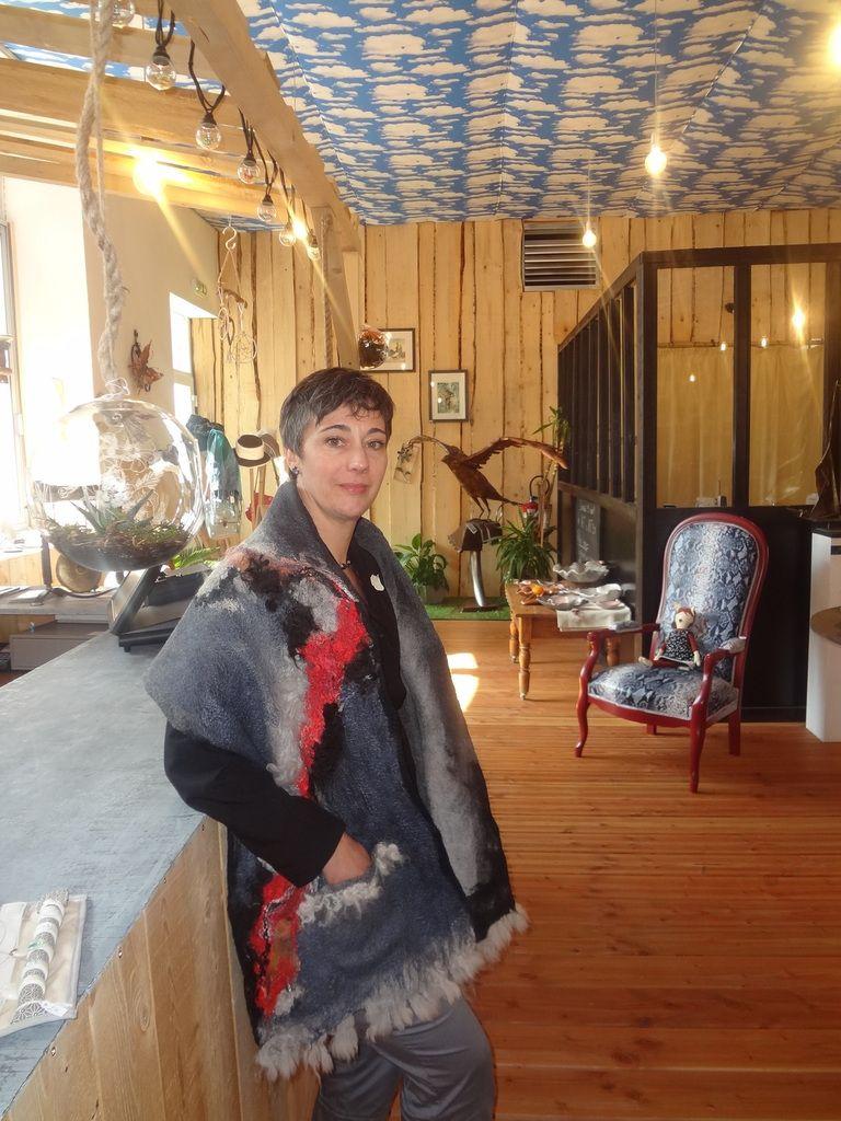 Magalie Goffart-Bazzoni, dans sa Cabane des Artisans, au milieu des créations des artisans-exposants et portant même un châle de création artisanale.