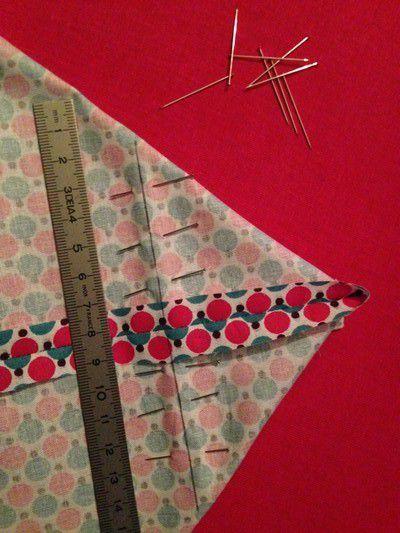 Plier le tissu couture contre couture de façon à obtenir une pointe en haut . Repérer et tracer la base d'un triangle de 14 cm sur chaque pointe de tissu et coudre sur le trait !