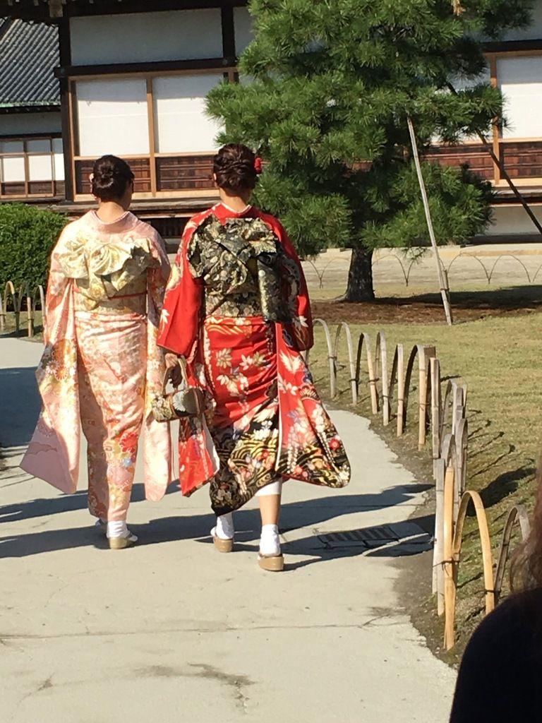 Les jeunes femmes en kimono traversant le parc
