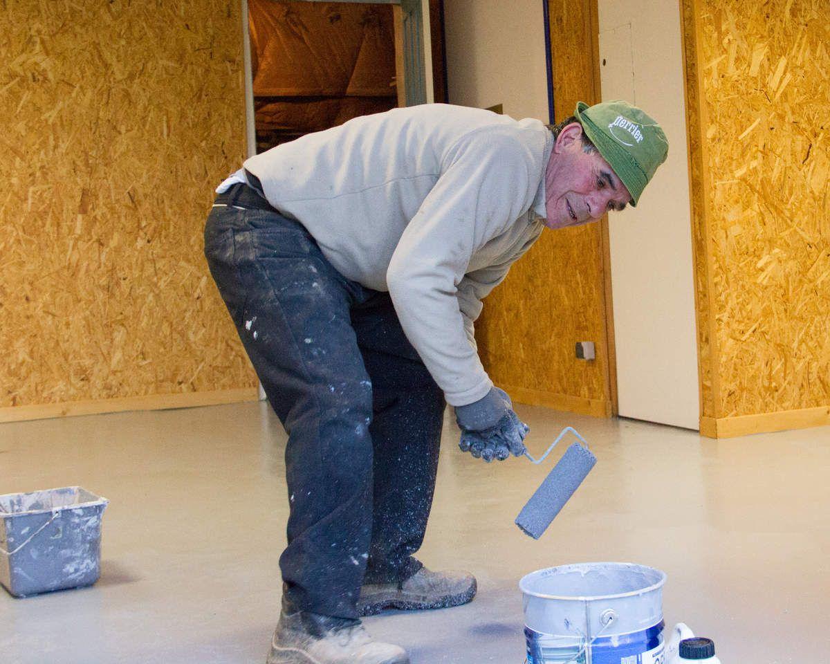 Manu à la peinture du sol dans le local vie, anciennement vestiaires