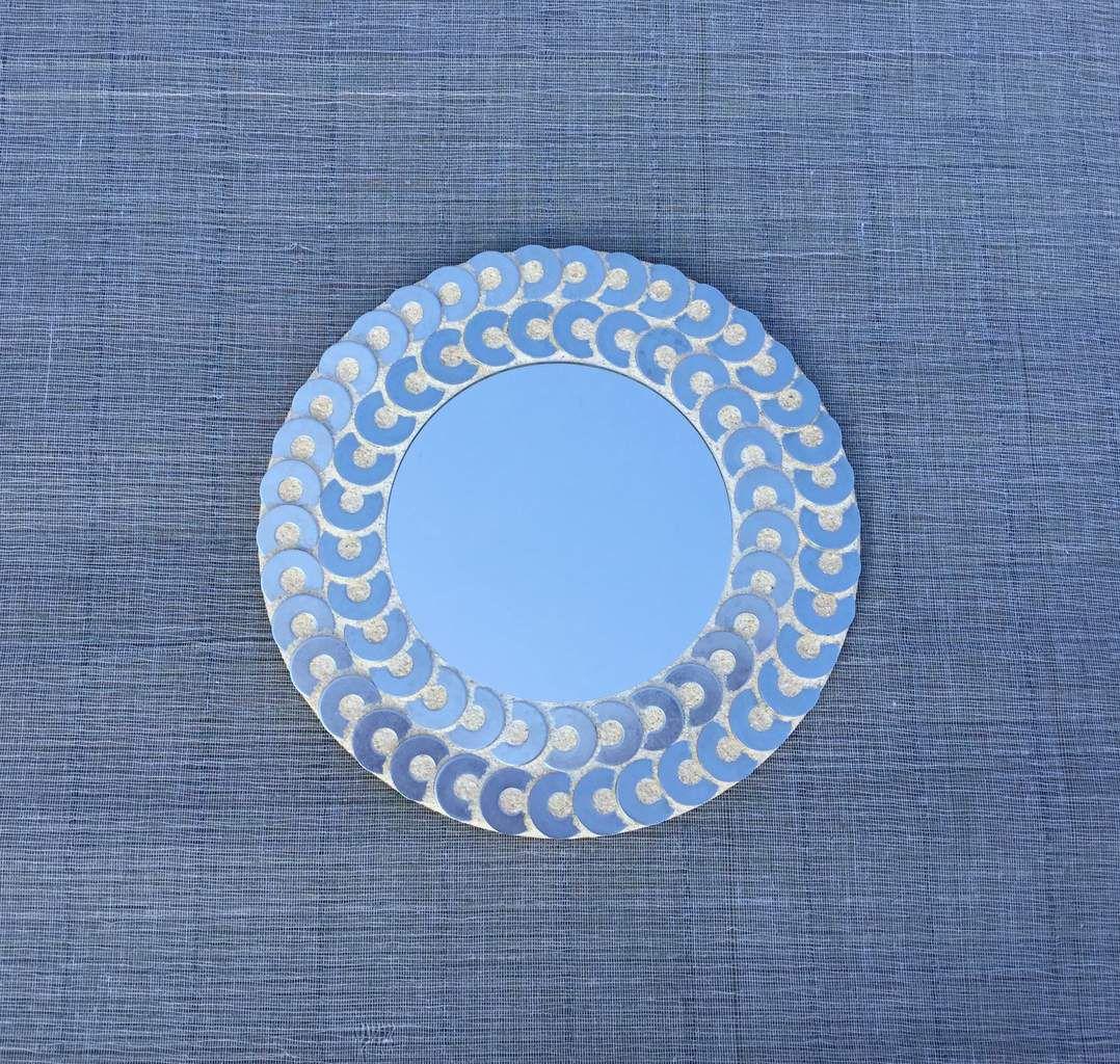 Miroir orné de rondelles de métal, joint type mosaïque. Diamètre total 26 cm.