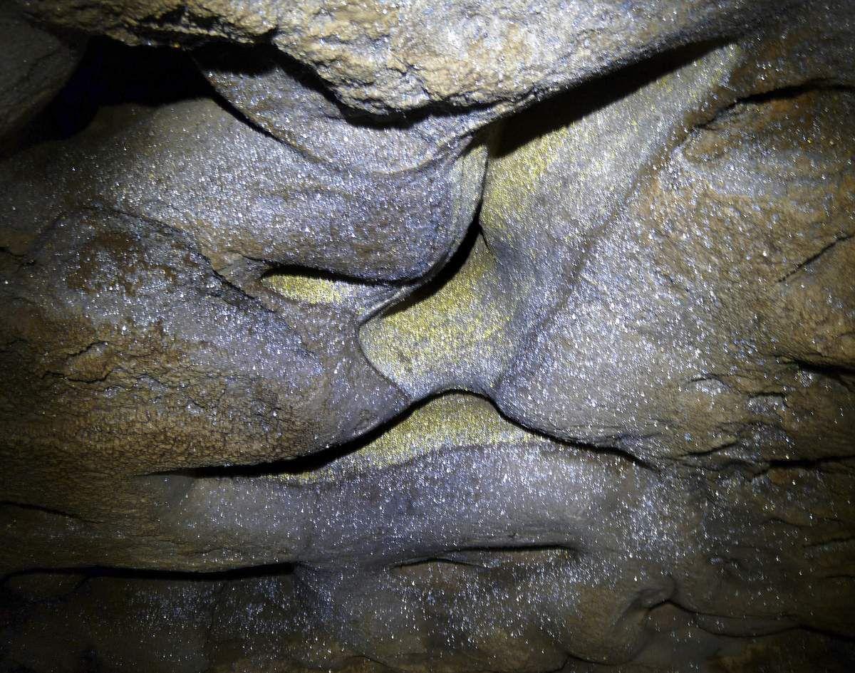 La calcite prise dans les gouttelettes brille comme de l'or à la lueur de nos frontales.