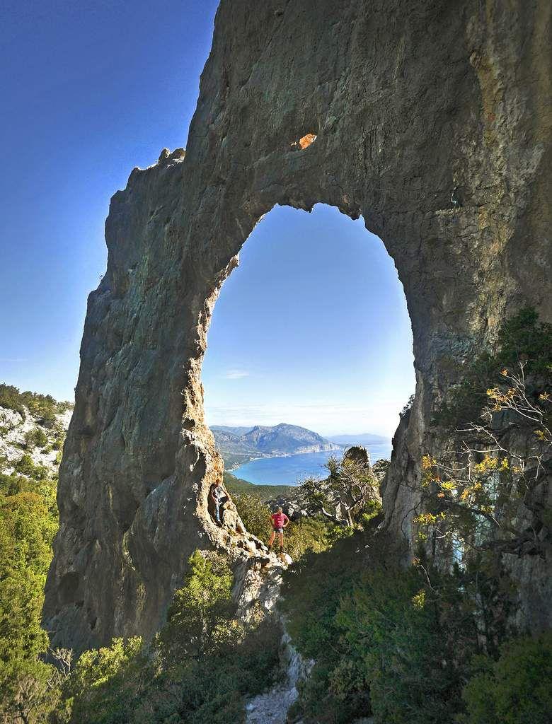 À travers l'arche de Lupiru, on aperçoit Cala Gonone et la coulée volcanique qui la domine.