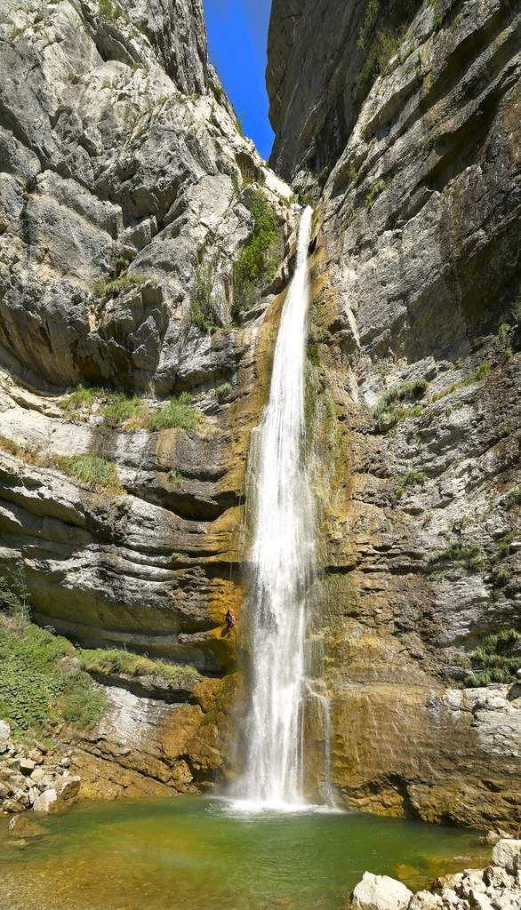 La cascade se jette dans une grande et profonde vasque. Les canyonistes, comme celui que l'on voit ici, arrivent dans l'eau, mais nos rappels de l'autre côté permettent toujours d'éviter de se mouiller.