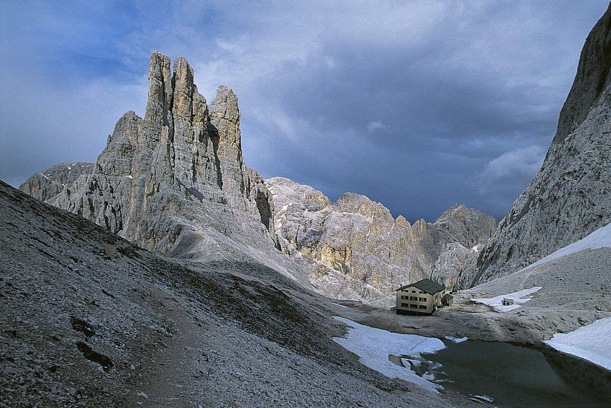 """Les tours de Vajolet et le refuge Re Alberto. Il s'agit de l'un des sites les plus célèbres de la région. Tita Piaz, """"le Diable des Dolomites"""", en avait fait son terrain de jeu à la fin du 19e siècle, convoquant volontiers la haute société à admirer ses exploits depuis le site du refuge. Les grimpeurs viennent toujours nombreux ici pour gravir les trois tours, dont la difficulté reste relativement modérée. Le spigolo Piaz (à gauche) est la voie la plus connue, et c'est notre objectif du jour."""