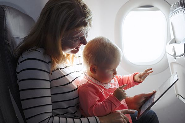 Mother and baby using tablet on flight - Shutterstock