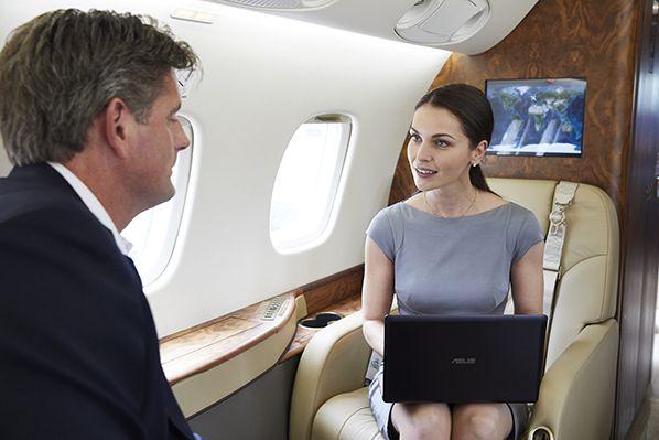 Homme et femme d'affaires à bord d'un jet privé Legacy