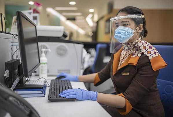 Guest Service Agent at Etihad Airways Medical Centre wearing the face shield