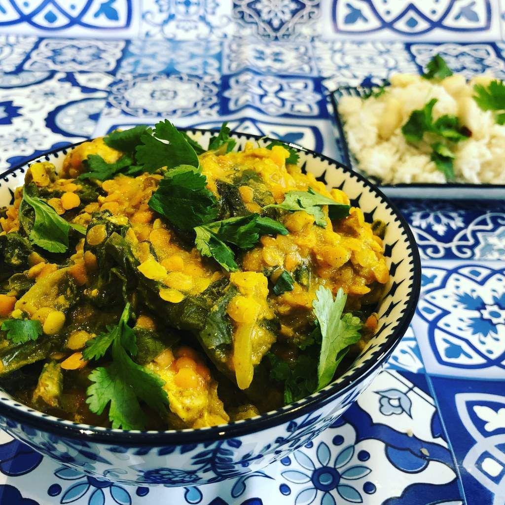 curry indien au poulet, aux lentilles corail et aux épinards dans une sauce au lait de coco et servi avec un riz basmati et des arachides fraiches