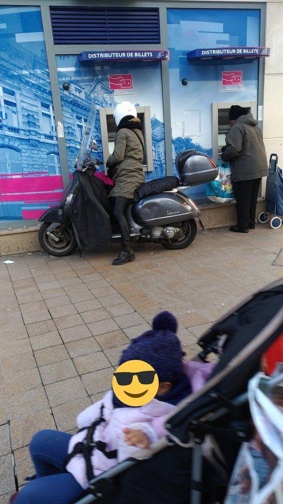 Femme sur un scooter sur un trottoir