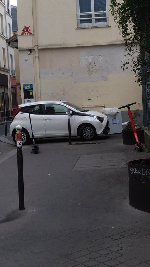 Trottoir envahi par des trottinettes et une voiture en circulation