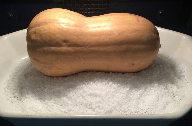 Courge butternut cuite entière sur du gros sel
